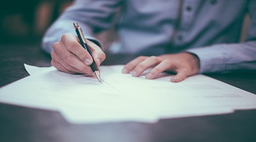 man signing papers third party risk management